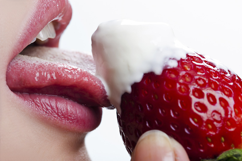 woman tastes strawberry and cream