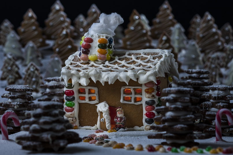 gingerbread house and biscuits decorated with icing and lollies (candy).